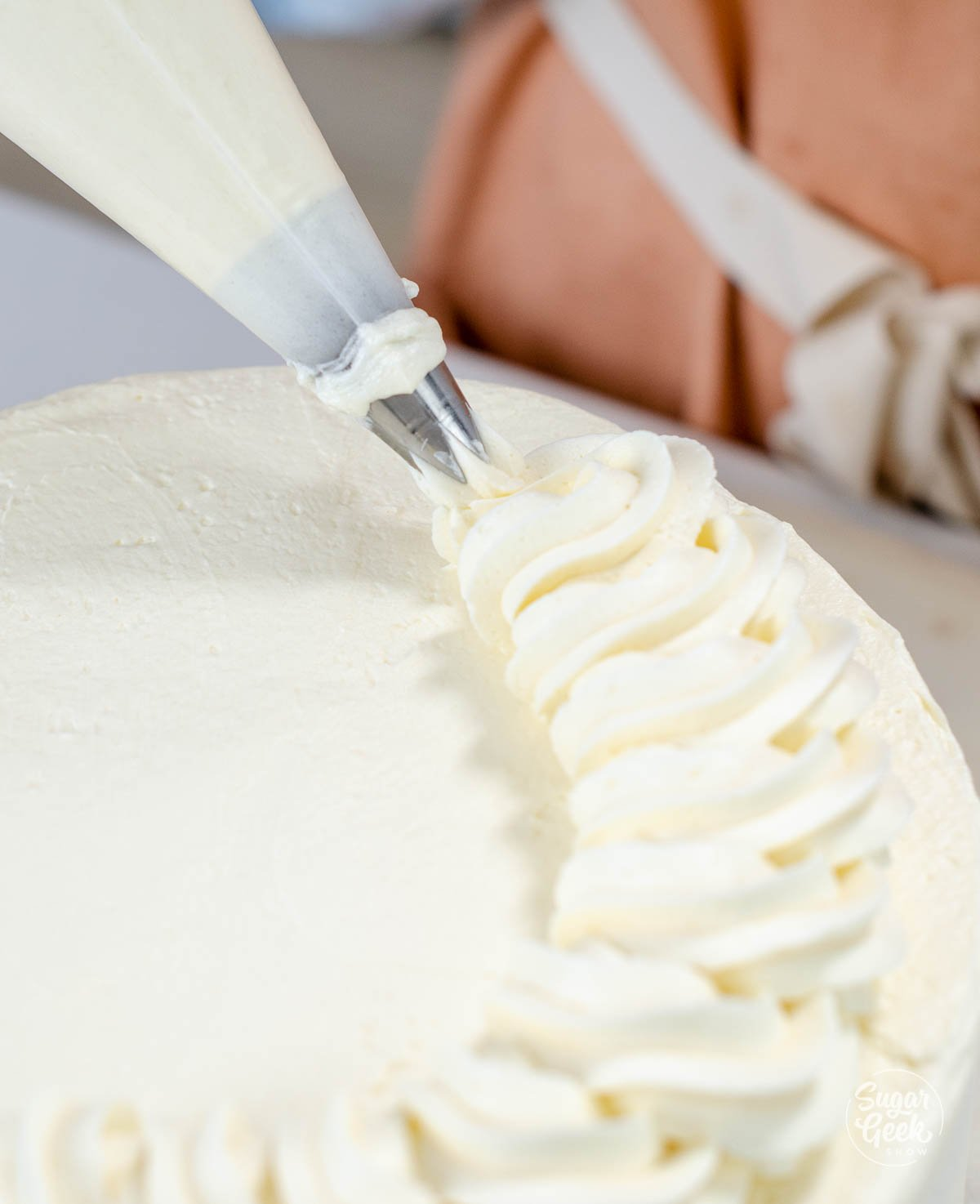 piping a rope border on top of the cake
