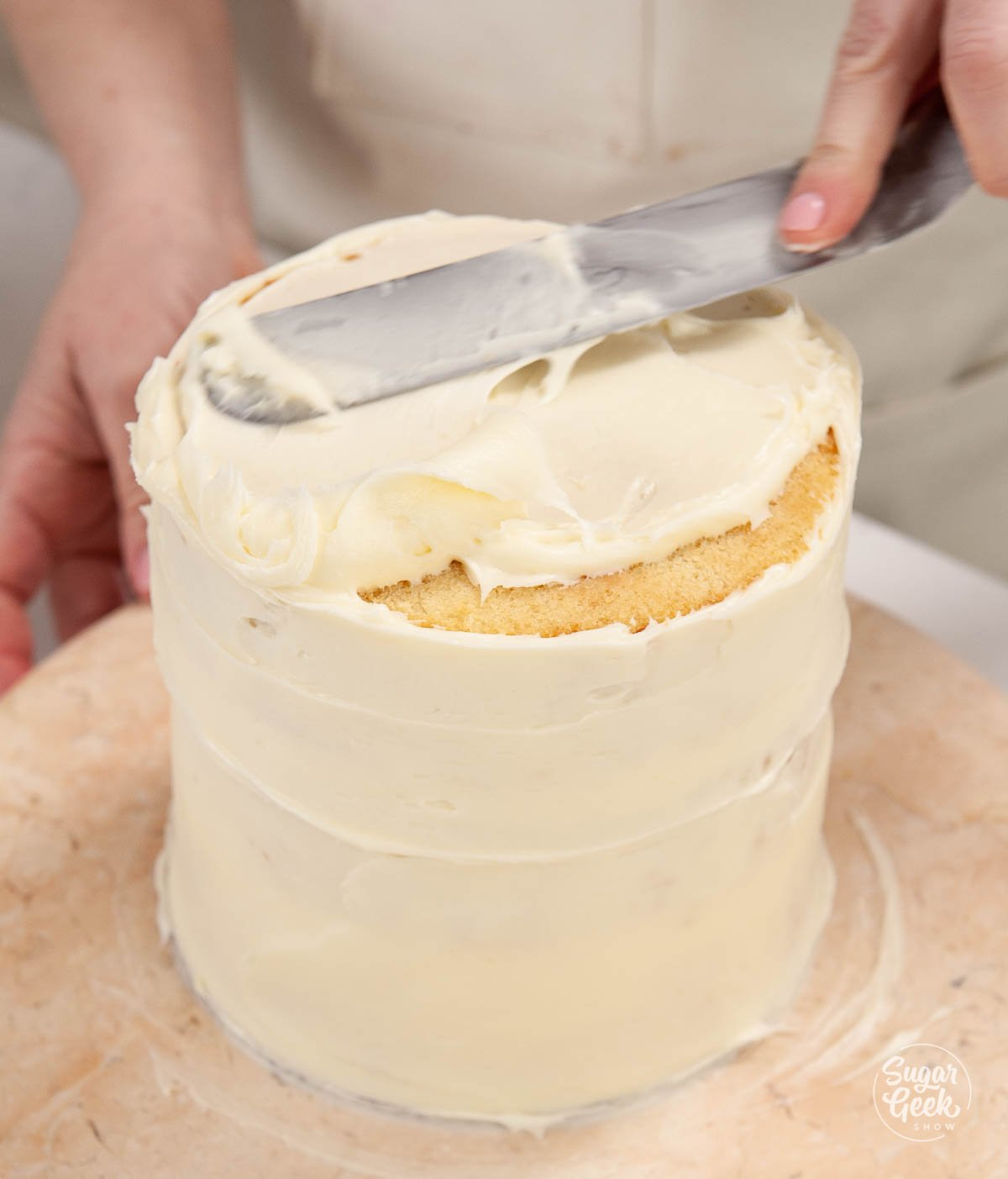 covering the lemon cake in a crumbcoat