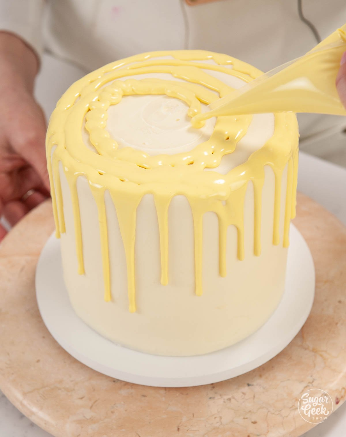 adding lemon ganache to the top of a lemon layer cake