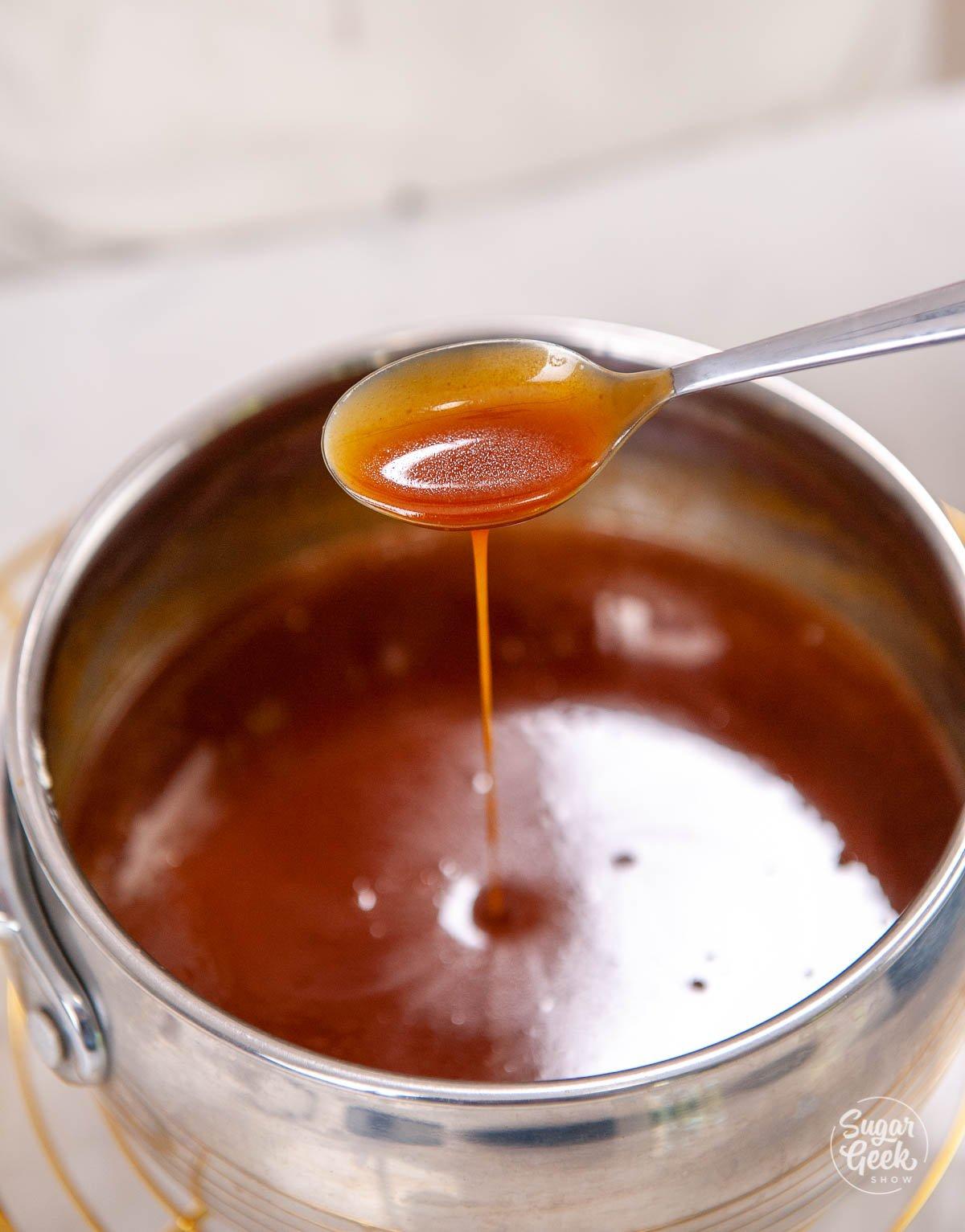 spoon dripping caramel sauce into sauce pan