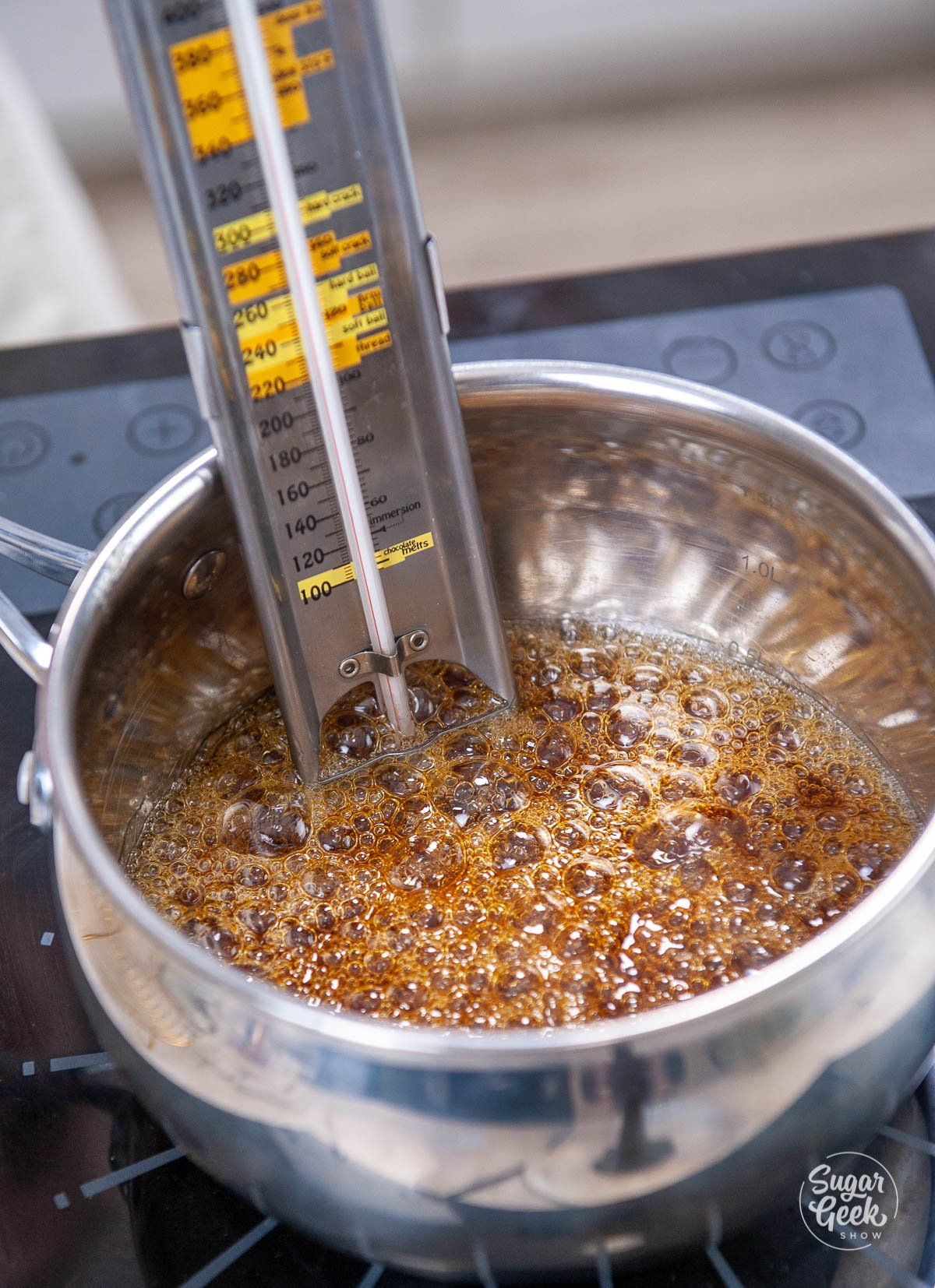 candy thermometer sitting inside pot of cooking caramel on stove top