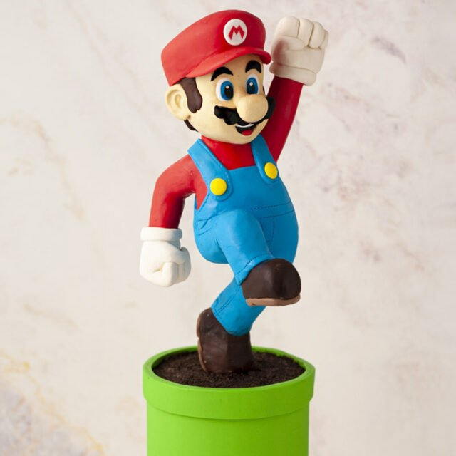 Cake scultped to look like Super Mario jumping on top of a green pipe