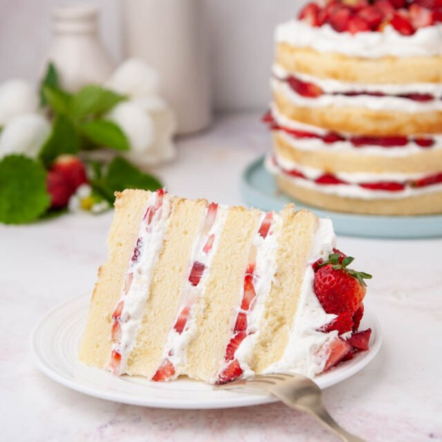 closeup of strawberry shortcake slice on a white plate