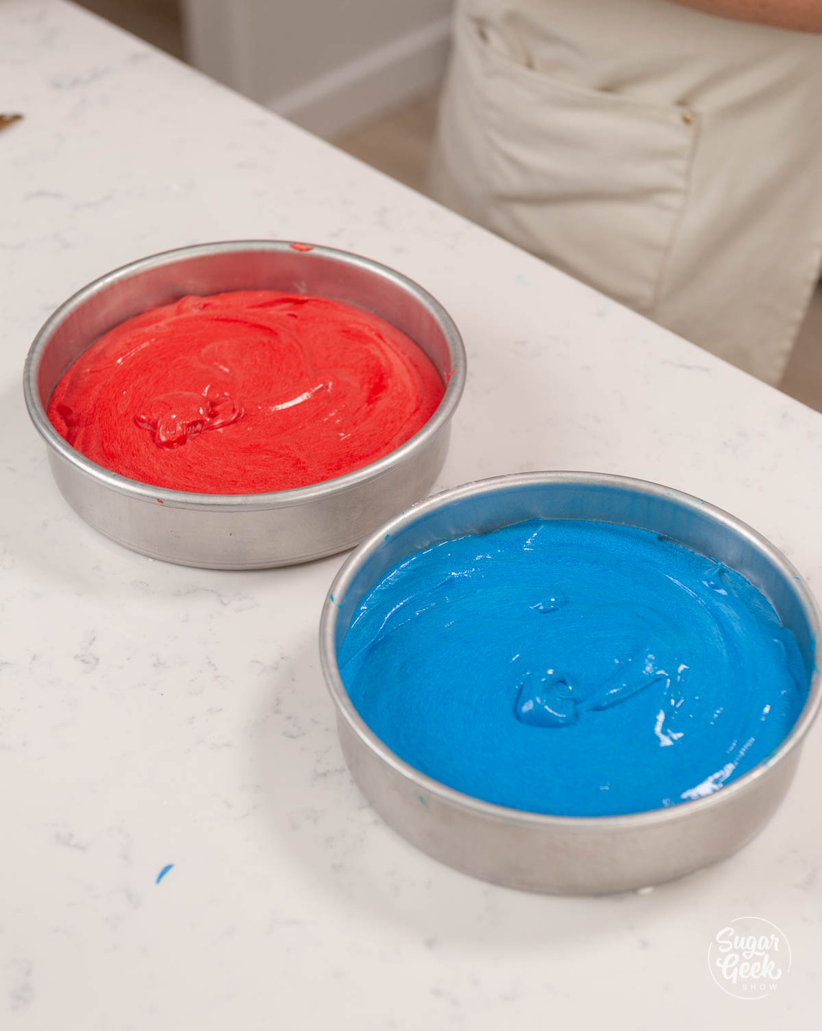 red and blue cake batter in cake pans