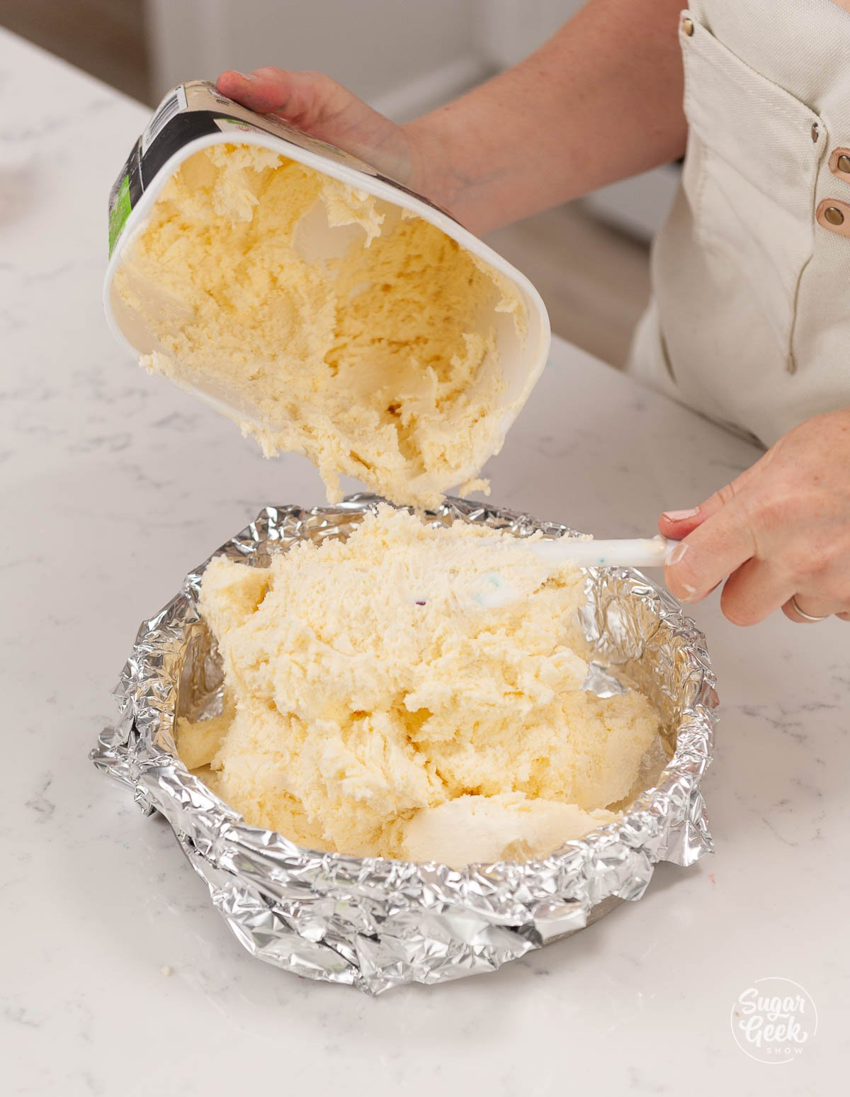placing softened ice cream into an aluminum foil lined cake pan