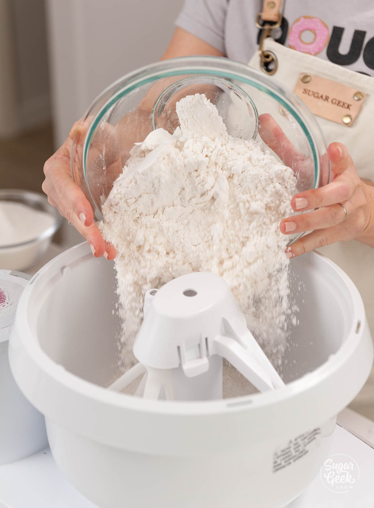 bowl pouring flour into a stand mixer mixing bowl