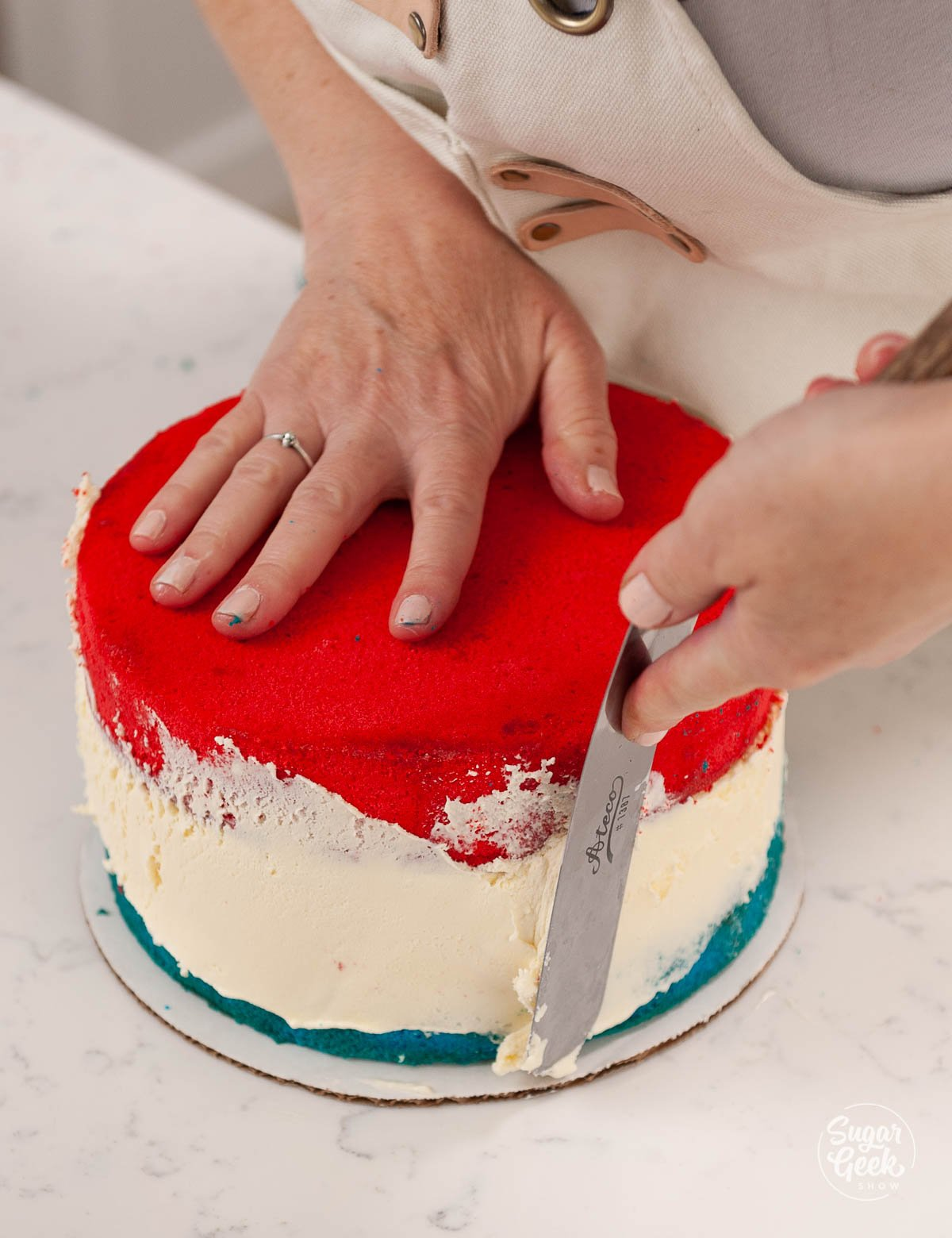 red cake layer on top of ice cream and blue cake layer