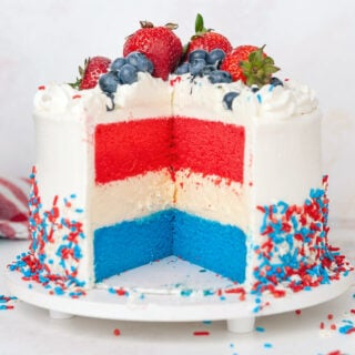 close up of red white and blue cake with slice taken out of the front