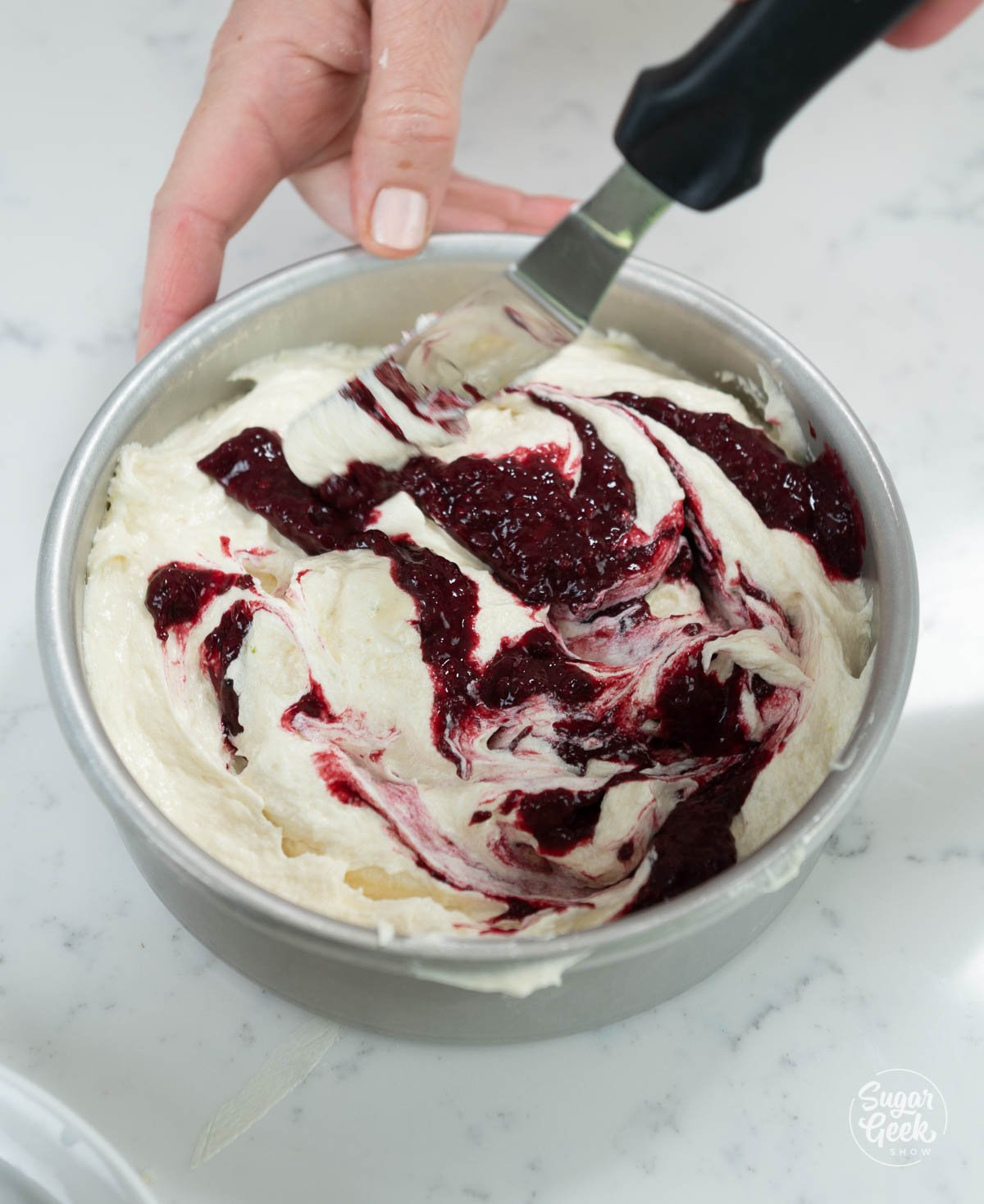 swirling blackberry puree into cake batter in pans