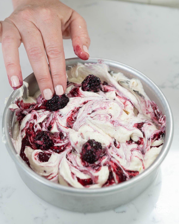 adding fresh blackberries to blackberry cake batter in cake pans