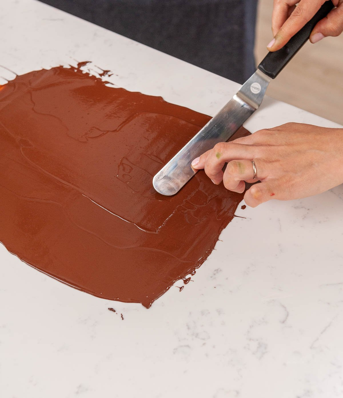spreading chocolate on acetate with an offset spatula