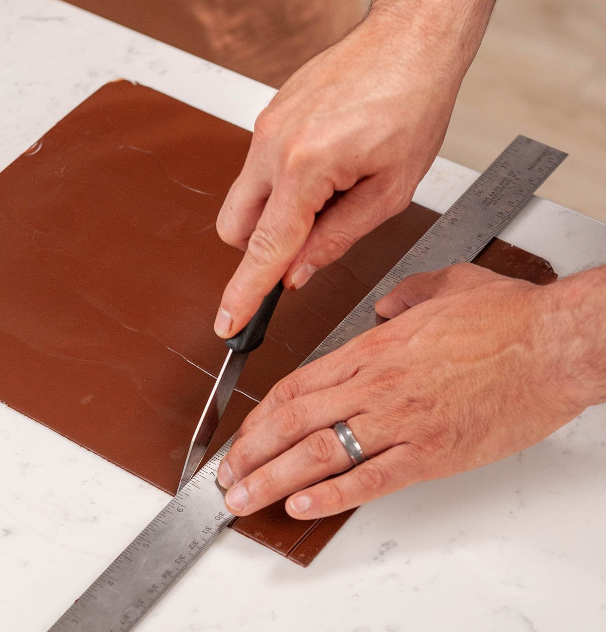 cutting chocolate squares on acetate with a knife and ruler
