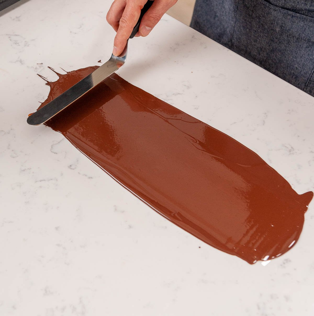 spreading tempered chocolate on acetate with an offset spatula