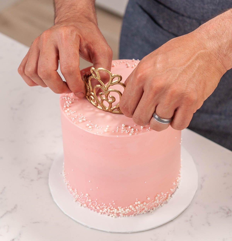 placing a chocolate tiara on top of the cake