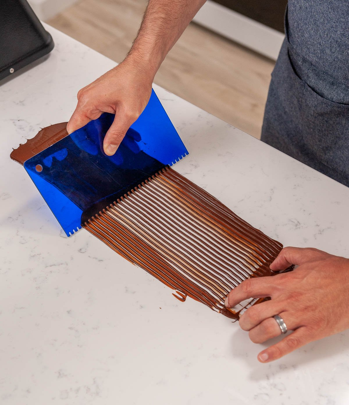 using a cake comb to scrape lines into chocolate on acetate