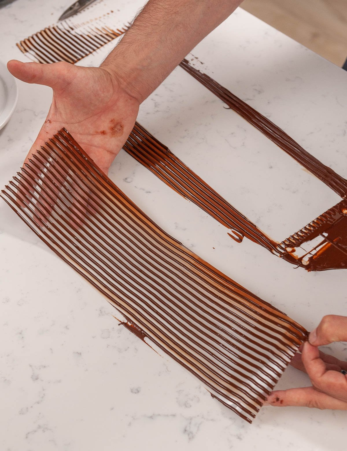 holding acetate with lines of chocolate on top