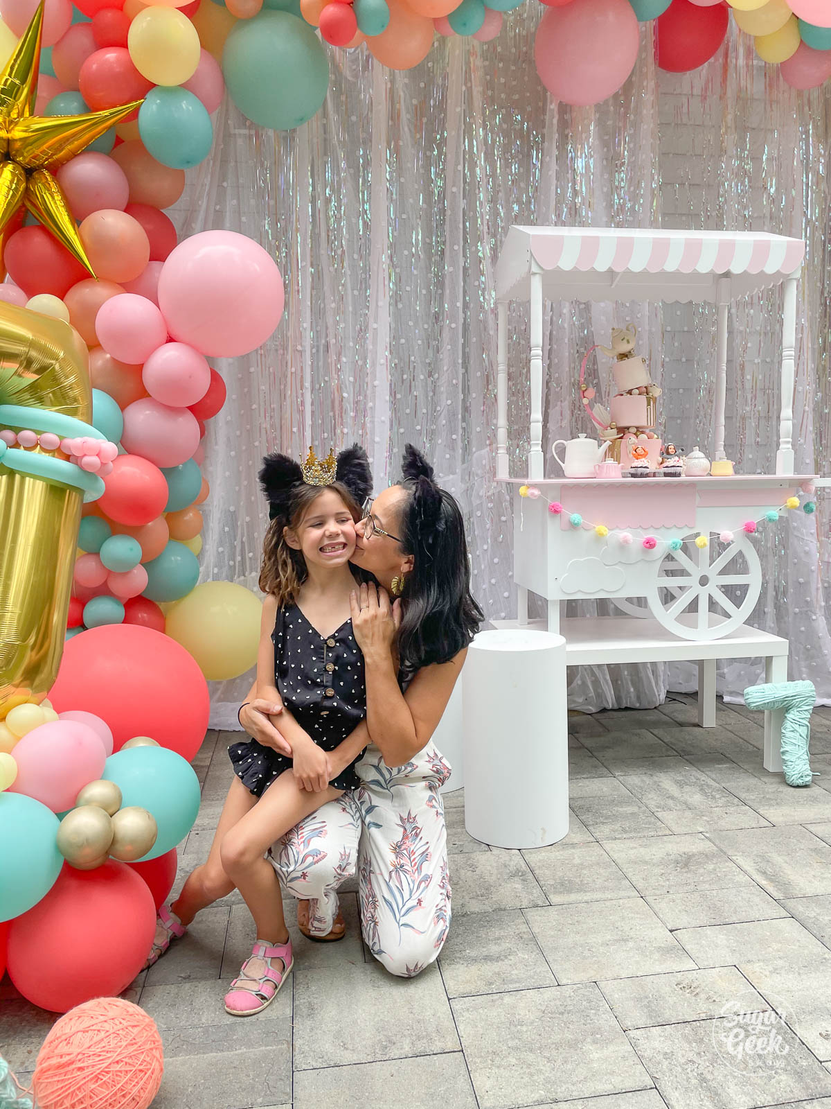 mom kissing daughter next to balloons