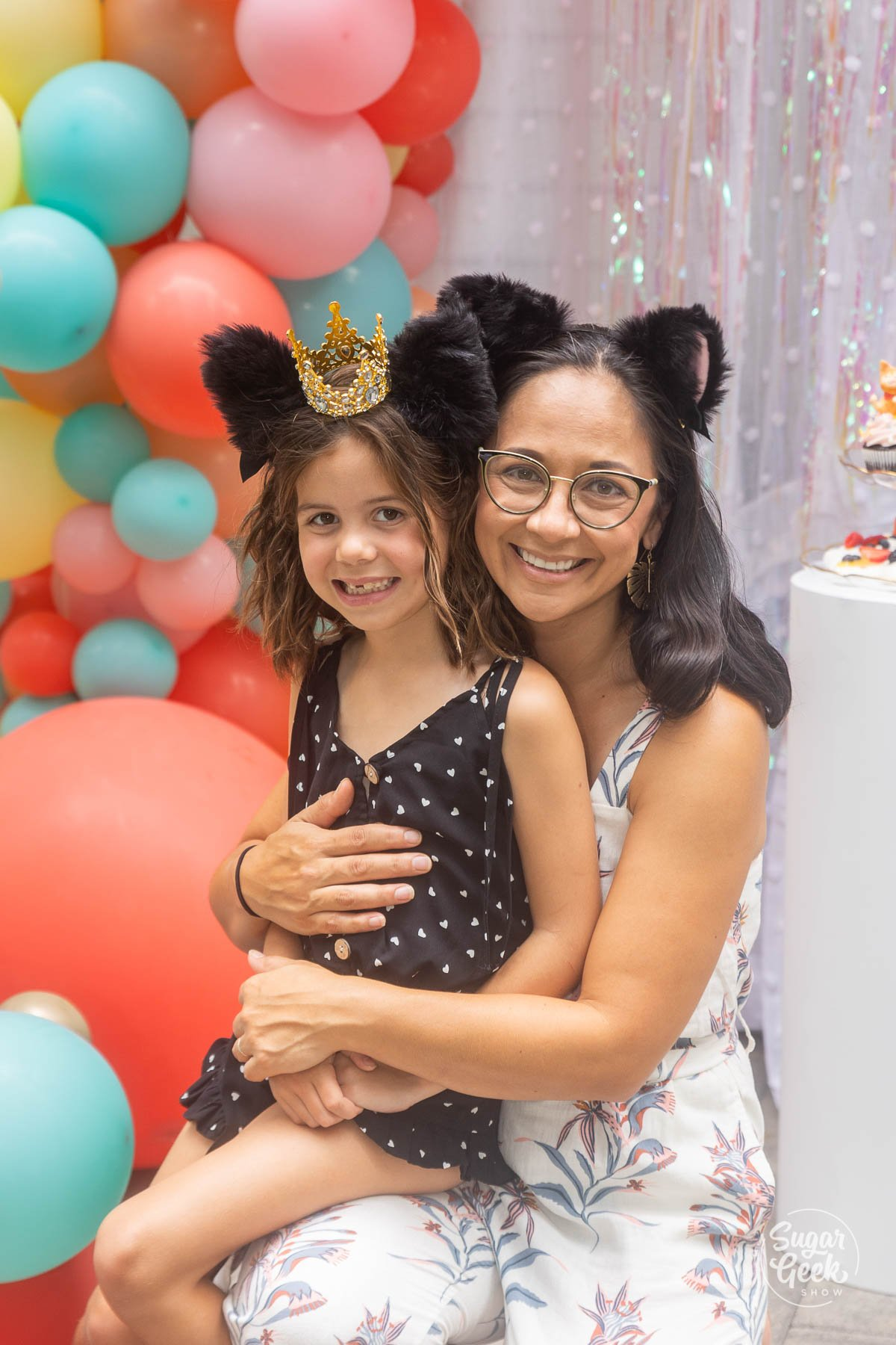 mom and daughter posing in cat ear headbands in front of balloons