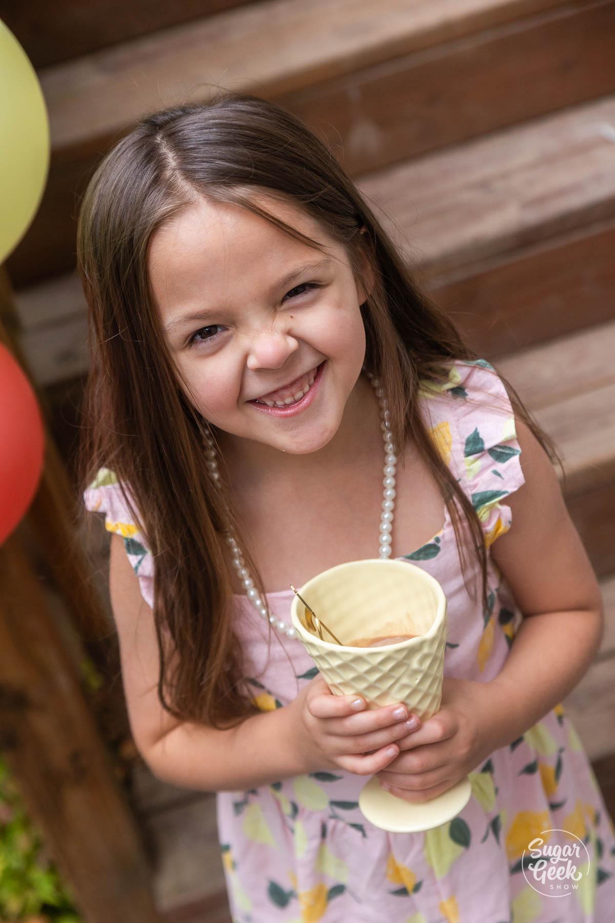 girl smiling with ceramic ice cream cone