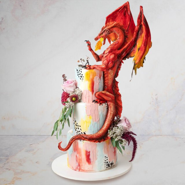 Wedding cake with a sculpted dragon sitting on top fighting bride and groom cake toppers