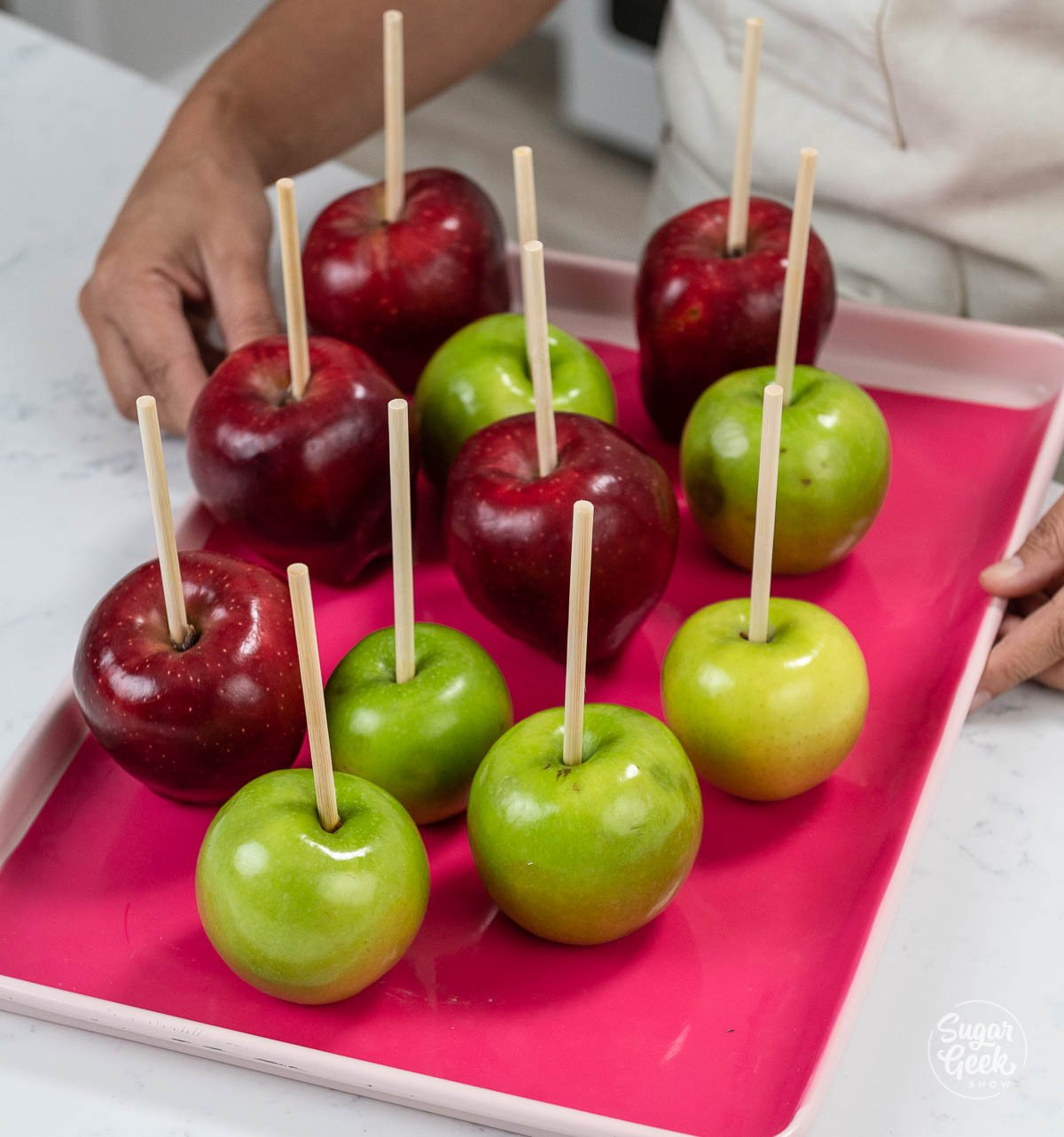 green and red apples on a sheetpan with a pink silicone mat