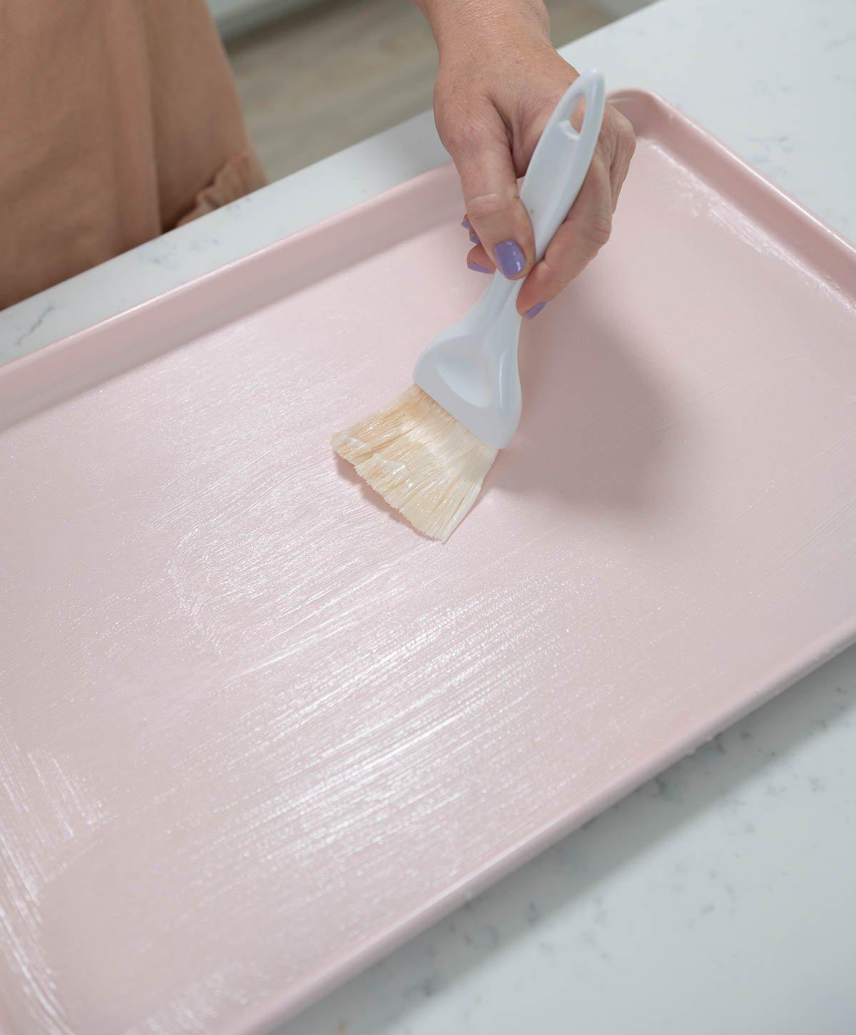 brushing cake goop on a pink sheet pan