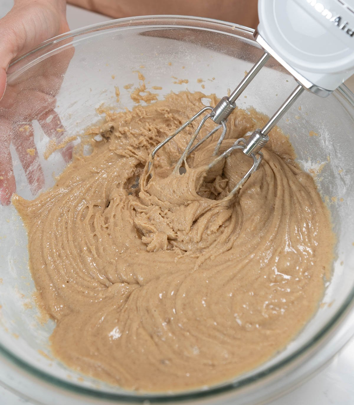 mixing texas sheet cake batter in a clear mixing bowl
