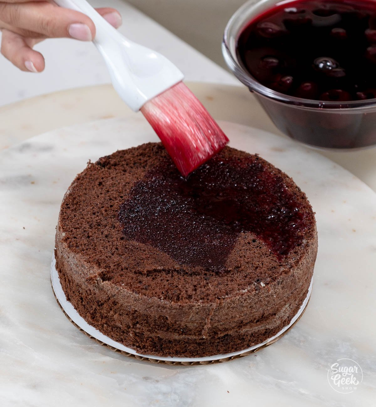 soaking a genoise cake layer with syrup