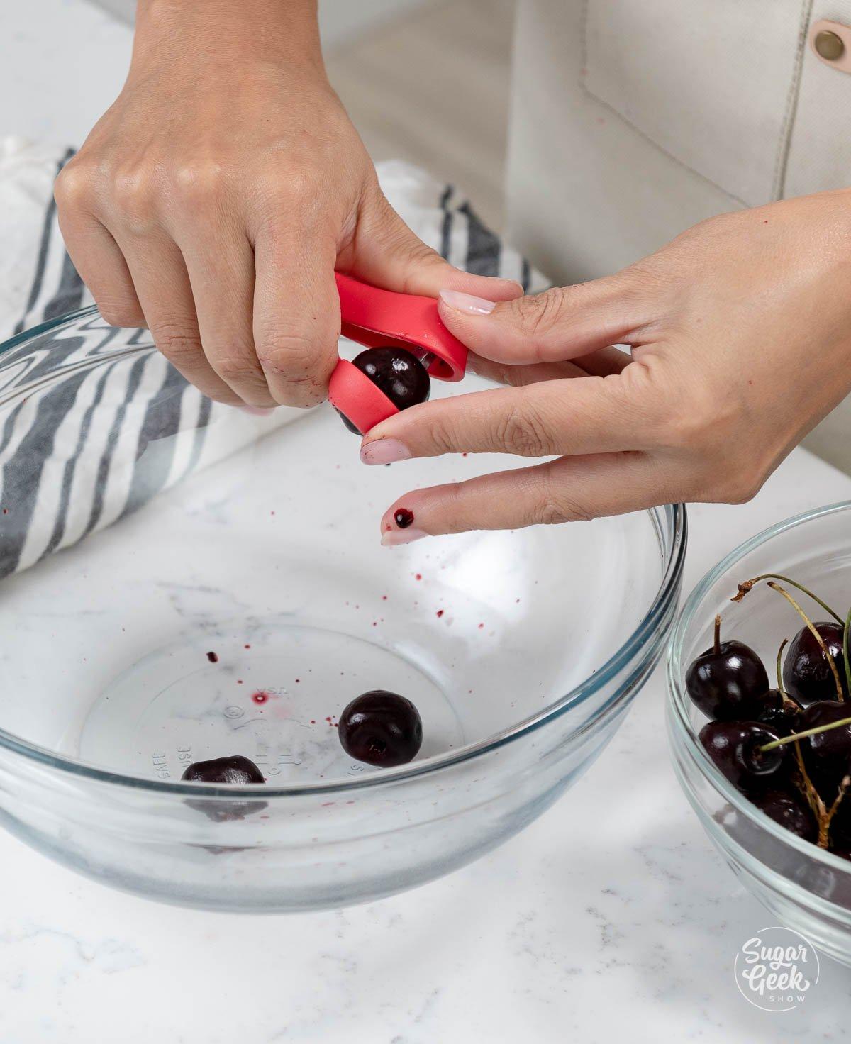 pitting fresh cherries into a bowl