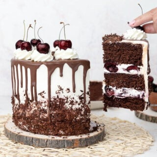 hand pulling a slice of black forest cake from the whole cake