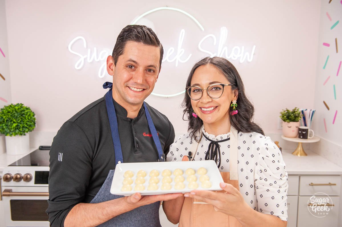 christophe rull and liz marek holding a tray of bonbons