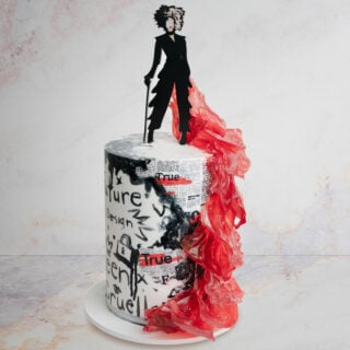 Cake with hand painted graffiti and an edible red dress with Cruella cake topper
